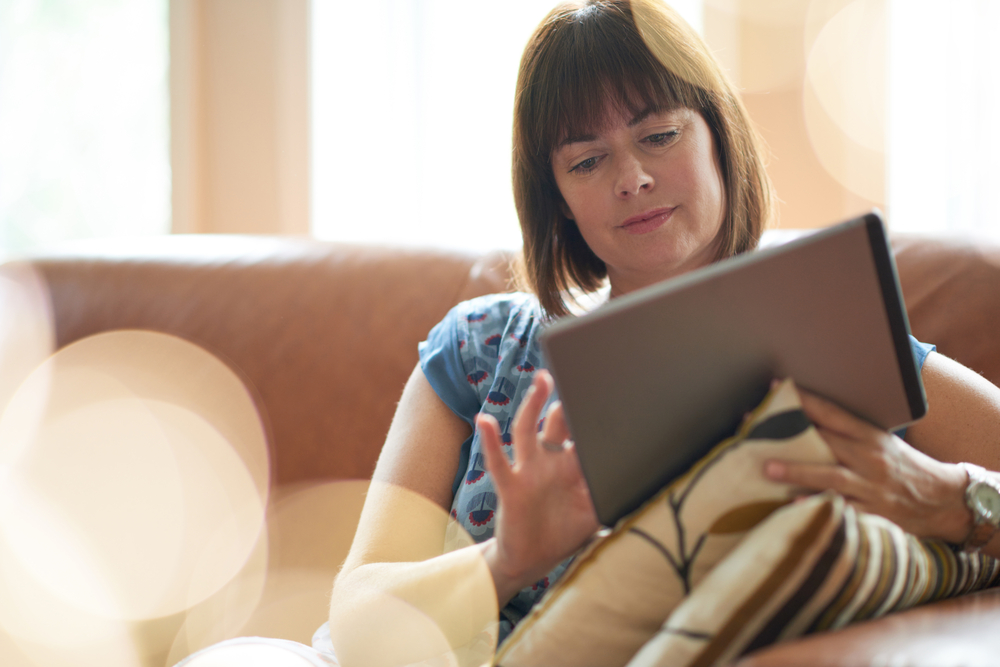 Mature woman browsing the internet on a digital tablet-1