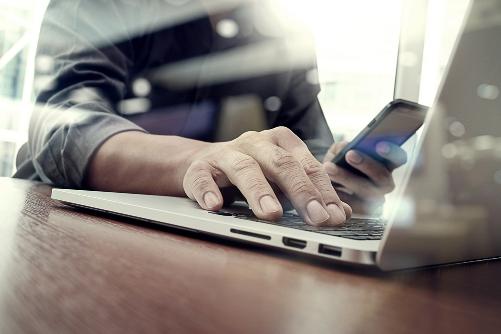 designer hand working and smart phone and laptop on wooden desk in office with london city background-1